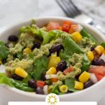 Southwestern salad with an avocado dressing in a white round bowl with a stainless steel fork and glass of water behind (vertical with title overlay)