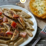 Cajun Chicken Pasta on a white plate with a fork to the right side and garlic toast in the background on a wooden surface (with title overlay)