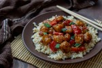 Quick & Easy General Tso's Chicken on a bed of rice on a round brown plate with bamboo chop sticks on top of a bamboo mat with a brown towel behind all on a wooden surface