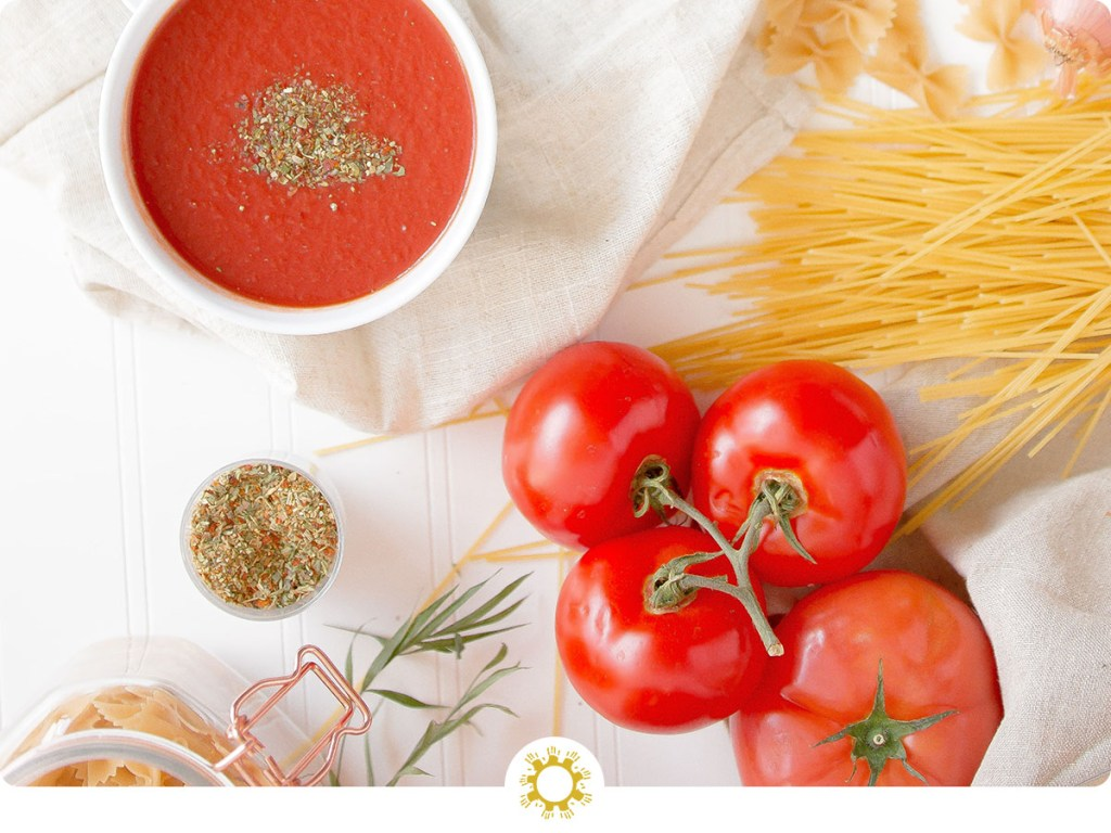 Tomatoes on a vine with uncooked pasta, seasonings in a bowl, and a bowl of tomato soup with a white towel on a white surface (with logo overlay)