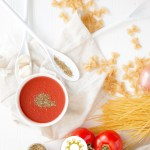 Tomatoes on a vine with uncooked pasta, seasonings in a bowl, and a bowl of tomato soup with a white towel on a white surface
