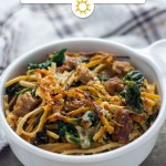 Sausage and Spinach Spaghetti Pie in a round white bowl next to a white and brown towel on a wooden surface (vertical with title overlay)