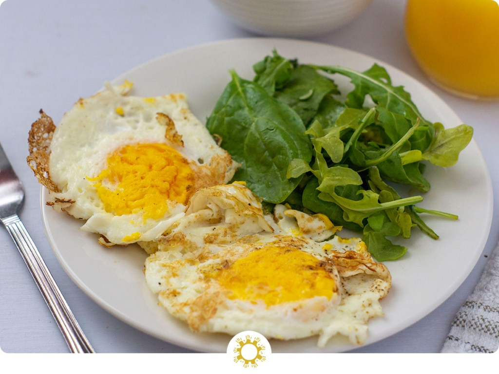 Fried Eggs Over-Hard on a white plate next to greens with breakfast potatoes and orange juice in the background (with logo overlay)