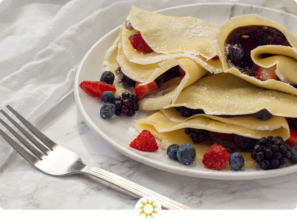 Multiple breakfast crepes filled with chocolate sauce and berries and garnished with powdered sugar on a white plate with a white napkin behind and a fork near the front on a grey marbled surface (with logo overlay)