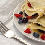 Multiple breakfast crepes filled with chocolate sauce and berries and garnished with powdered sugar on a white plate with a white napkin behind and a fork near the front on a grey marbled surface (with title overlay)