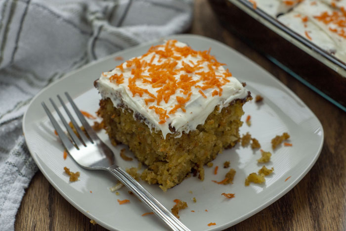 A slice of Carrot Cake with Pineapple Filling and cream cheese frosting on a white plate with a metal fork next to a white towel and the pan of cake in the background on a wooden surface