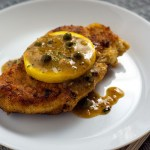 Chicken piccata topped with lemon on a round white plate with a fork and grey placemat (vertical with simple title overlay)