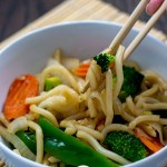 Round white bowl of vegetable lo mein with a pair of chopsticks pulling out some noodles, onion, and broccoli on top of a bamboo placement on a wooden surface (vertical with title overlay)