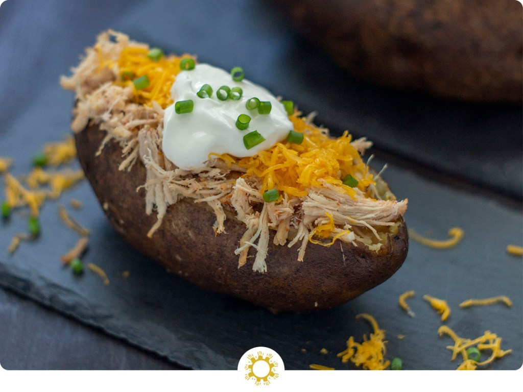BBQ Pork Potatoes: baked potato sliced down the center covered with pulled pork, shredded cheddar cheese, a scoop of sour cream, and garnished with sliced green onion on a slate surface with other potatoes behind all on a dark wooden surface (with logo overlay)