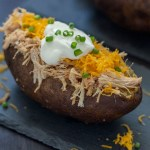 BBQ Pork Potatoes: baked potato sliced down the center covered with pulled pork, shredded cheddar cheese, a scoop of sour cream, and garnished with sliced green onion on a slate surface with other potatoes behind all on a dark wooden surface