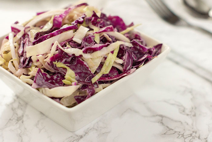 Coleslaw in a square white bowl on a white and grey marbled background