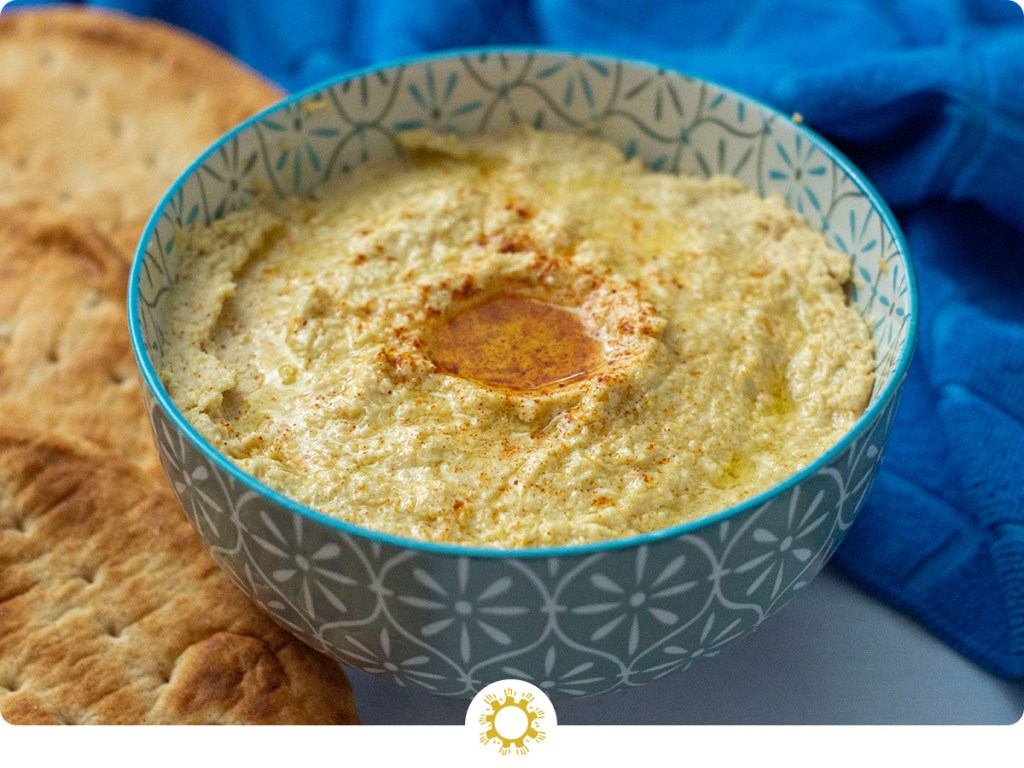Garlic hummus in a blue patterned bowl with pita bread on the side (with logo overlay)