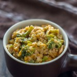Cheesy Rice Casserole with Chicken and Broccoli in a brown serving dish with a brown and white towel behind all on a wooden surface (vertical with title overlay)