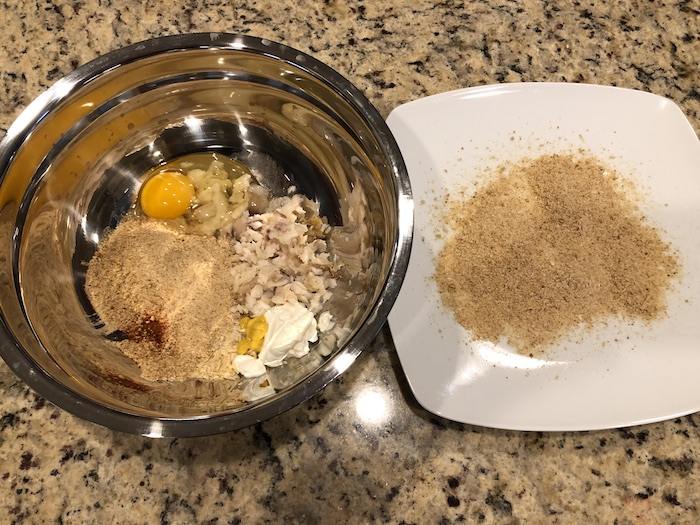 Shredded fish, breadcrumbs, eggs, and seasonings in a stainless steel bowl next to a white plate covered with breadcrumbs all on a granite surface