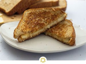 Classic Grilled Cheese Sandwich wedges on a round white plate with sliced bread and cheese behind all on a white surface (with logo overlay)