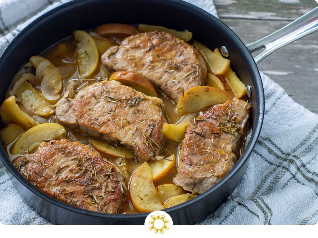 Cooked seasoned pork chops on a bed of cooked sliced onions and apples with an herb juice in a large skillet on top of a white and grey towel all on a wooden surface (with logo overlay)