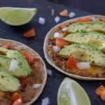 Bean and Cheese Tostadas on a dark granite surface with lime pieces around them (with title overlay)