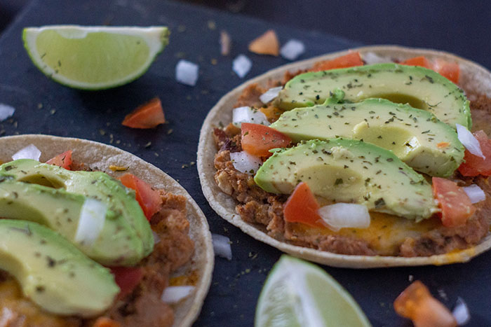 Bean and Cheese Tostadas on a dark granite surface with lime pieces around them