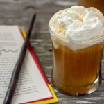 Glass of Butterbeer topped with whipped topping next to an open book and a magic wand with a pitcher of Butterbeer in the background all on a wooden surface