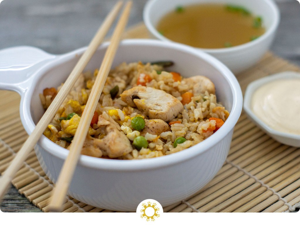 Chicken fried rice in a white bowl with wooden chopsticks across the top next to a bowl of clear onion soup and a small dish of white sauce on a bamboo placemat (with logo overlay)