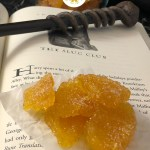 Crystallized Pineapple on a piece of wax paper sitting on an open Harry Potter book with a wand on top with a glass bowl of crystallized pineapple behind the book all on a black and white marble surface (vertical with title overlay)
