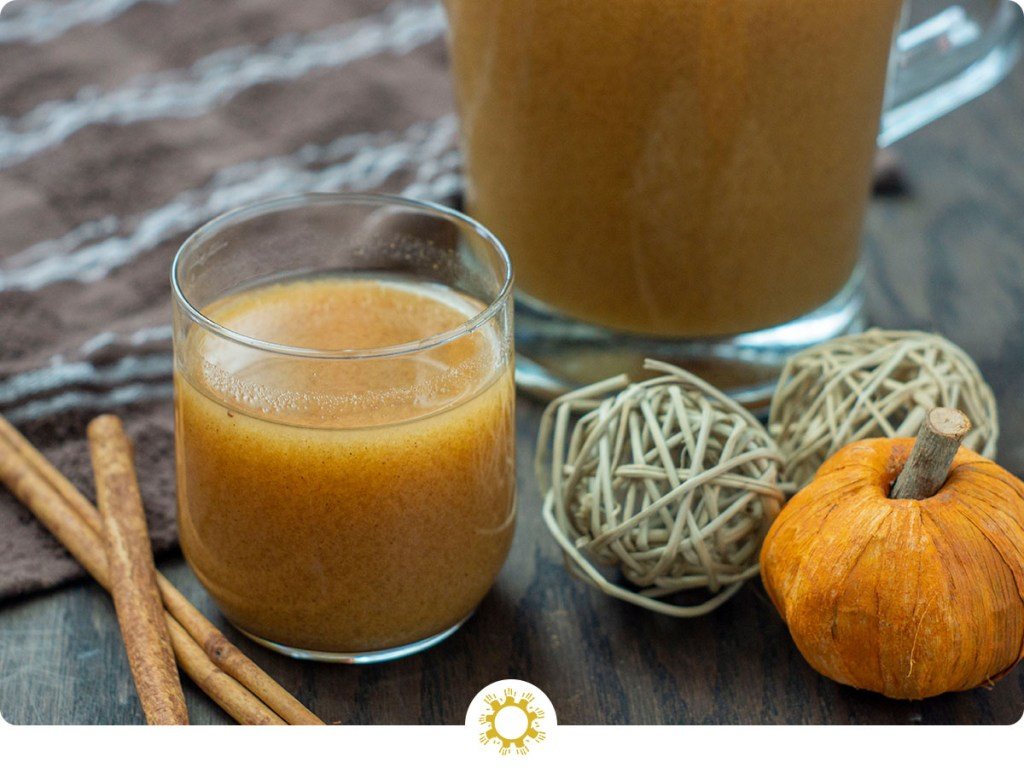 Pumpkin Juice in a small glass cup with a glass pitcher behind and cinnamon sticks to the side on a wooden surface (with logo overlay)