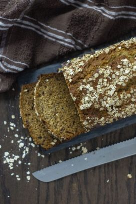 Banana Bread covered with oats on a slate serving plate next to a brown towel and a bread knife on a wooden surface (vertical)
