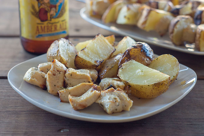 Plate with cooked chicken and potatoes with skewers in background and bottle of beer