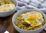 Leek orzo with fried egg garnished with parsley in two round white bowls with a stainless steel fork and a white and brown towel all on a wooden surface