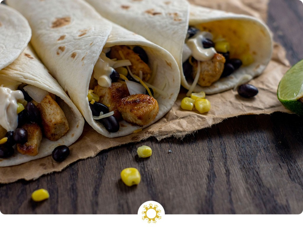 Three chipotle chicken tacos with a few ingredients falling out on a piece of brown parchment paper next to a lime wedge on a wooden surface (with logo overlay)
