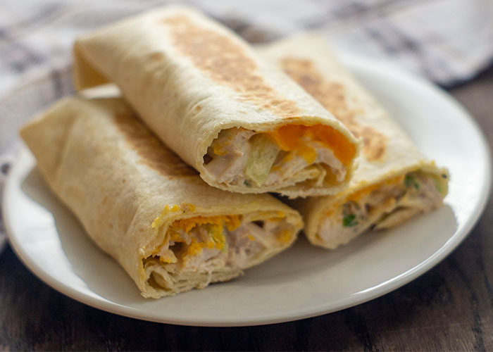 Side view of three crispy chicken wraps with the ends cut off to show the cheese and chicken mixture inside stacked on a small white round plate with a white and brown towel behind all on a wooden surface