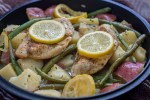Cast-iron with diced tomatoes, lemon slices, green beans, and cooked chicken covered in seasonings on a brown towel