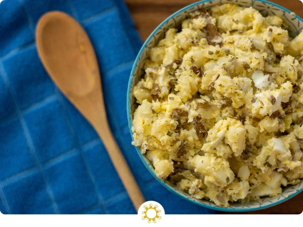 Homemade potato salad in a blue bowl next to a blue towel and wooden spoon (with logo overlay)