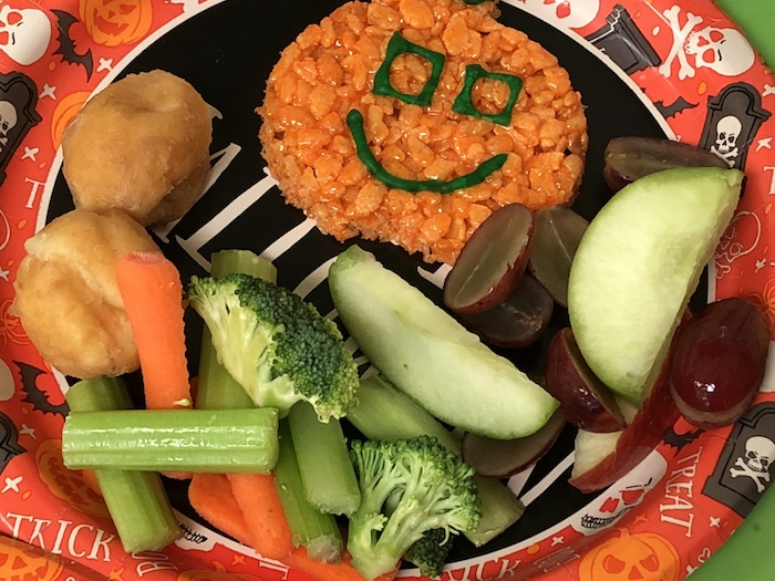 Preschool Halloween party fruit, veggies, and desserts on a round Halloween plate