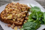 Corned beef hash breakfast toast: cooked corned beef hash mixed with scrambled eggs on a piece of toast next to spinach leaves on a white plate all on a wooden surface