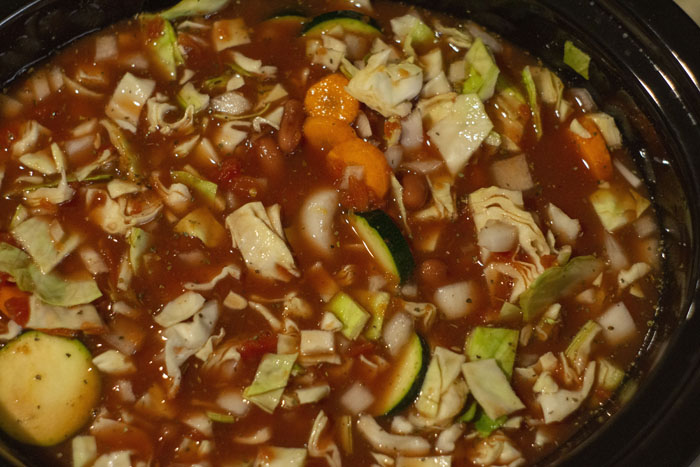 Sauce ingredients mixed in with chopped vegetables in a slow cooker
