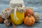 Pumpkin puree in a decorated mason jar next to fall decorations on a wooden surface