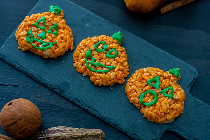 Pumpkin-shaped rice krispies with faces in green icing on a slate serving board on a dark wooden surface with fall decorations