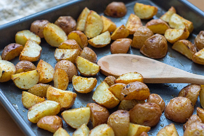 Roasted Potatoes with a wooden spoon on a metal baking sheet next to a tan towel on a light wooden surface