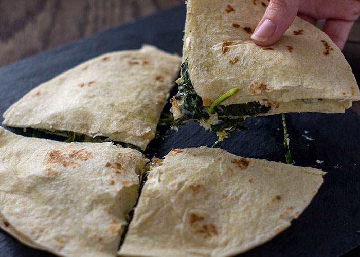 Spinach artichoke quesadilla cut into quarters with a woman's hand holding one piece up over a slate board on a wooden surface
