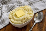 Garlic mashed cauliflower with a pat of butter on top in a white bowl next to a stainless steel spoon in front of a white and grey towel all on a wooden surface