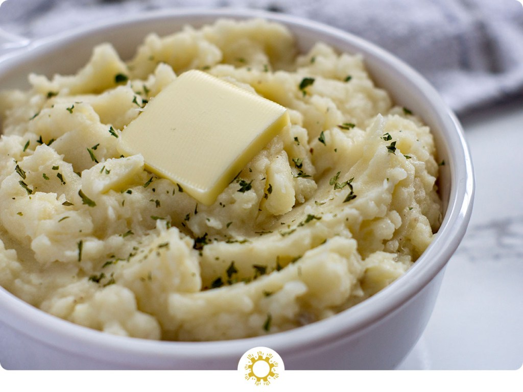 White bowl with creamy homemade mashed potatoes sprinkled with parsley and topped with a pat of butter (with logo overlay)