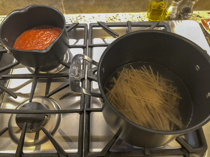 Saucepan with spaghetti sauce on the back burner of a gas stove with a pot of spaghetti noodles on the front burner