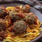 Spaghetti and Homemade Meatballs on a round brown plate next to a brown towel on a wooden surface (vertical with title overlay)