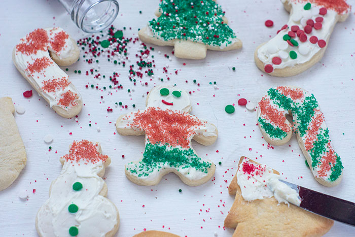 Christmas sugar cookies on a white surface with some frosted and decorated and a few unfrosted with spilled sprinkles