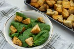 Italian-Style croutons on top of spinach leaves in a white bowl on top of a white and brown towel next to a metal baking sheet