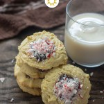 Stack of peppermint chocolate ganache thumbprint cookies surrounded by crushed peppermint and a glass of milk and brown towel behind all on a wooden surface (vertical with title overlay)