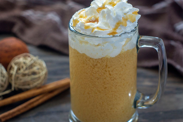 Glass mug of spiked hot apple cider topped with whipped cream and caramel sauce with fall decorations behind all on a wooden surface