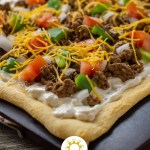 Baked taco pizza on a baking stone on a wooden surface (vertical with title overlay)