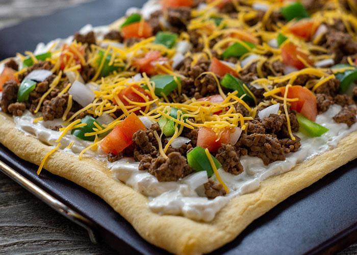 Baked taco pizza on a baking stone on a wooden surface
